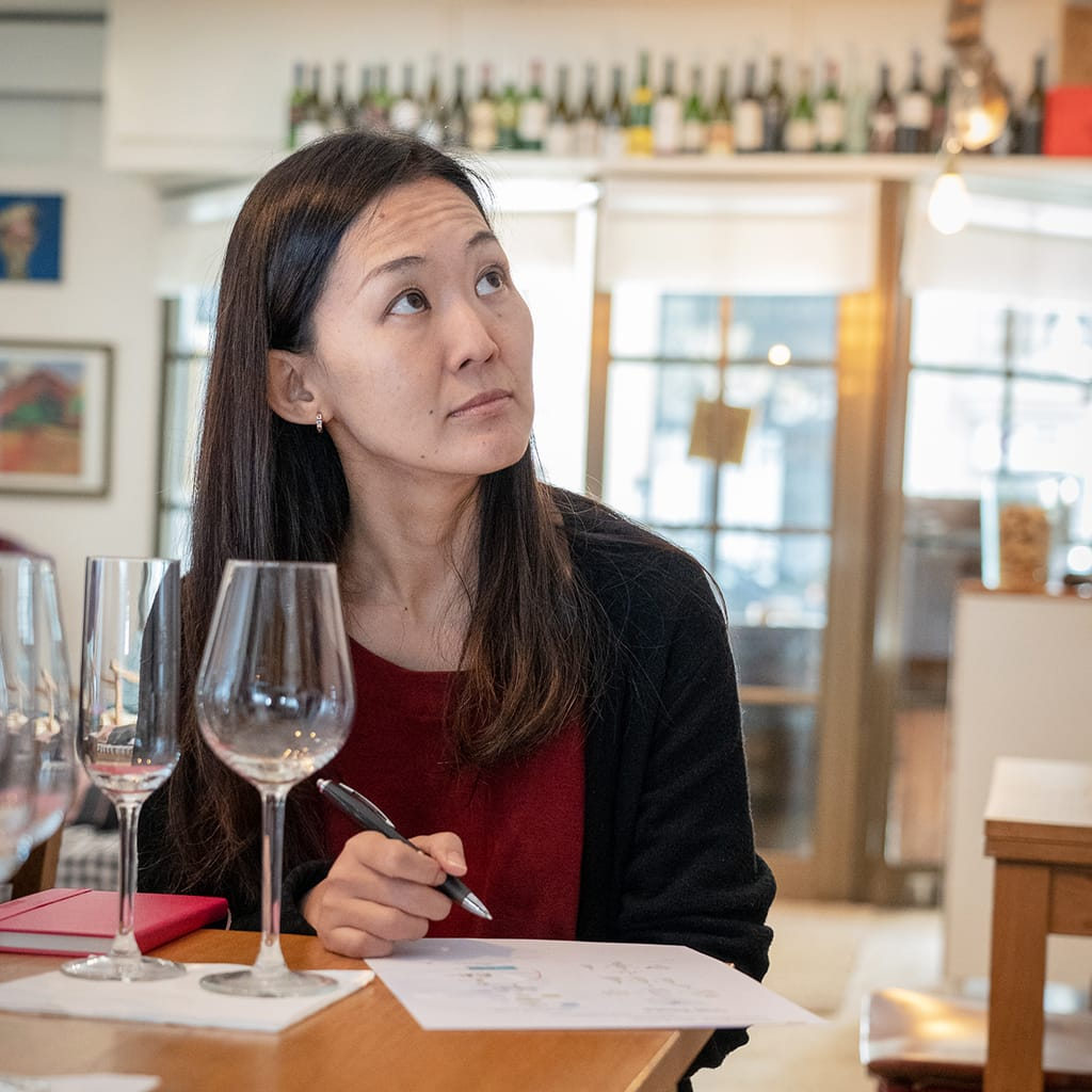 Woman Learning About Wine with Wine Glass and Wine Bottles in Background