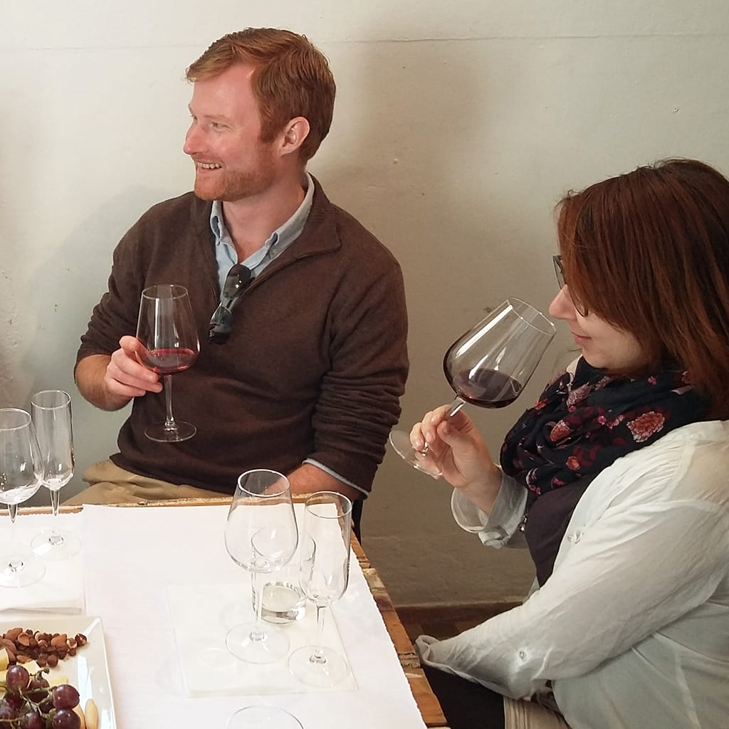 Man and Woman Enjoying Wine, Woman Smelling Wine Aromas in Glass