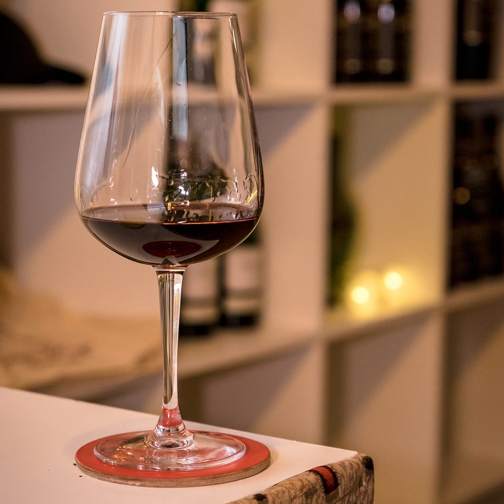 Wine Glass Showing Red Wine and Wine Shelves in the Background